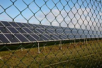 Solar panels behind chain link fence (thumbnail)