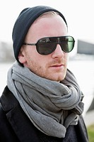 Hipster in grey scarf and sunglasses