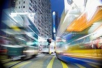 Buses moving through a city at night, blurred motion