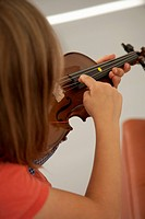 Girl plucking the string of a violin