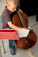 Boy playing cello with sheet music in the foreground