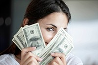 Woman peeking behind hundred dollar bills