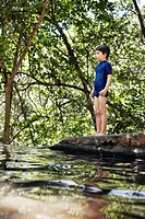 Boy standing by river in forest