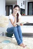 Woman sitting on books and reading