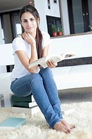 Woman at home sitting on books and reading