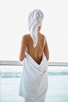 Woman wrapped in towel looking at sea view from balcony