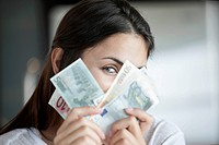 Woman peeking behind euro notes