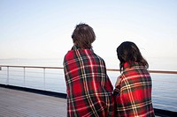 A couple on a ship deck, wrapped in blankets, looking at view, Seattle, Washington, USA