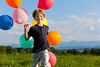 Boy with colorful balloons in grass