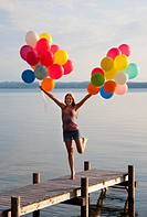 Teenage girl holding balloons on pier