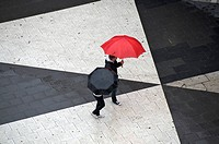 Two pedestrians with umbrellas