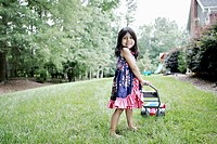 A young girl with a toy lawn mower pretending to mow the lawn