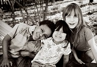 Three cheerful kids in a backyard (thumbnail)