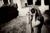A young girl using a camera