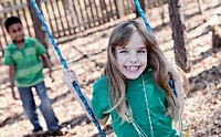 A cheerful girl on a swing being pushed by a boy, focus on girl
