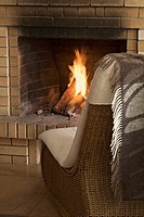 A wicker chair in front of a roaring fire