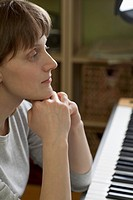 A woman leaning on an upright piano, looking pensive
