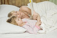 A mother and her young daughter lying in bed, reading a book