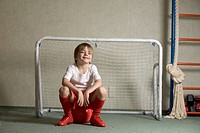 A young boy sitting on a soccer ball in front of a soccer goal