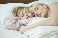 A mother and her young daughter sleeping a bed side by side