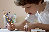 A boy drawing with a pencil