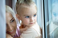 A mother and daughter looking out a window