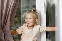 A young laughing girl pushing window curtains apart