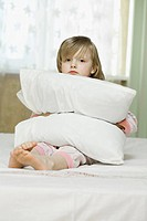 A sad looking little girl squeezing a pillow