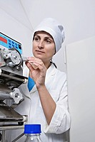 A lab technician adjust a knob on diagnostic medical equipment