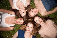 Five female friends lying in the grass in a circle looking sensually at the camera