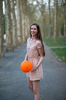 A young woman holding an orange ball, standing in a park (thumbnail)