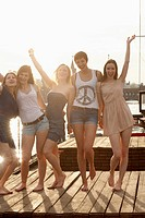 Five young female friends celebrating on a jetty, Spree River, Berlin, Germany