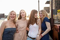 Four female friends standing side by side, Spree River, Berlin, Germany