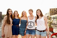 Five cheerful young female friends standing a row, Spree River, Berlin, Germany (thumbnail)