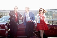 Three rockabilly friends leaning against a vintage car