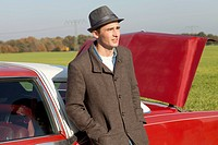 A young rockabilly man leaning against a vintage car in the country (thumbnail)