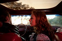 A rockabilly couple in the front seat of a vintage car