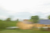 Buildings and landscape in blurred motion viewed from a moving train (thumbnail)