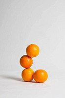 Oranges stacked precariously, studio shot