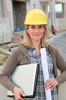 Woman engineer with security helmet standing on construction site