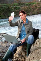 Woman scientist testing quality of water in river