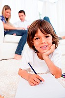 Smiling little boy drawing lying on floor