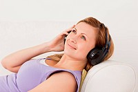 Attractive blond_haired woman listening to music lying on the so