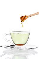honig tropft von einem honiglöffel in grünen tee
