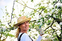 Young woman gardening _ in apple tree orchard