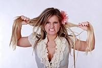 Junge blonde Frau rauft sich wütend die Haare