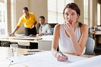 Woman at desk looking over plans