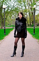 Attractive girl girl in a jacket on the road in the park