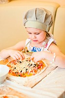 Little girl adding cheese in pizza