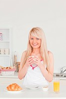 Young blonde woman having her breakfast in the kitchen